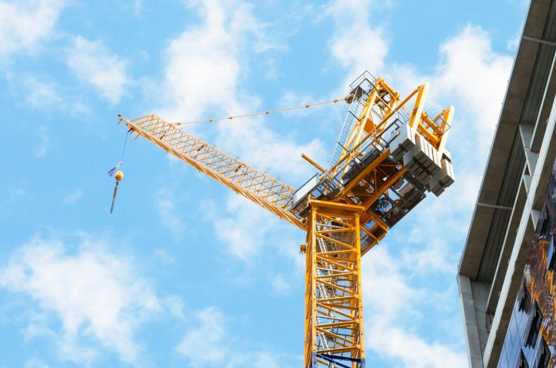 Close up construction crane next to bulding blue sky