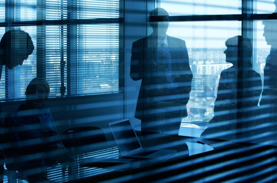 People in meeting room behind blinds