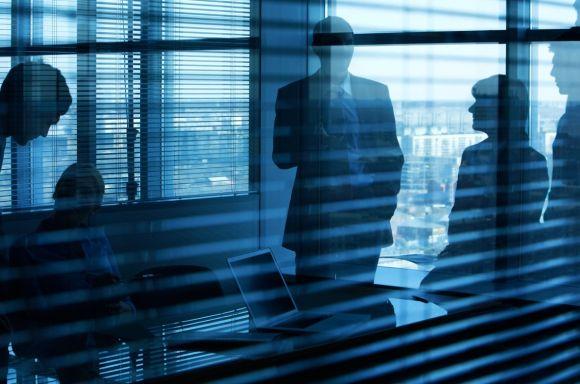People in meeting room behind blinds